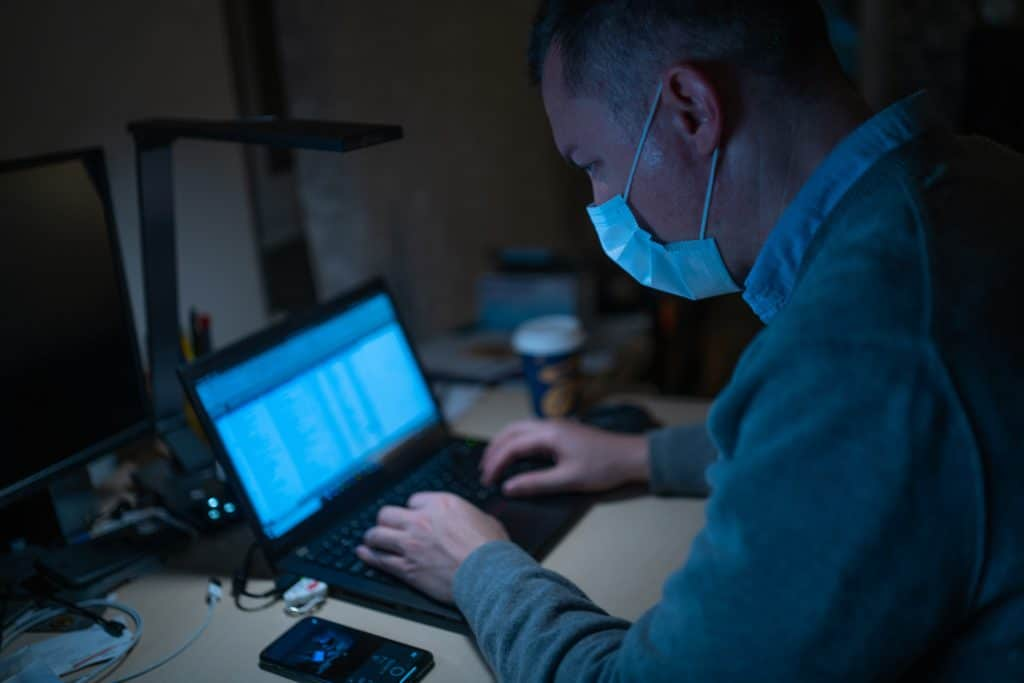 Man in mask searching online on computer